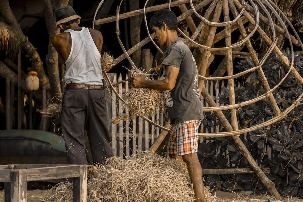 two men holding hays