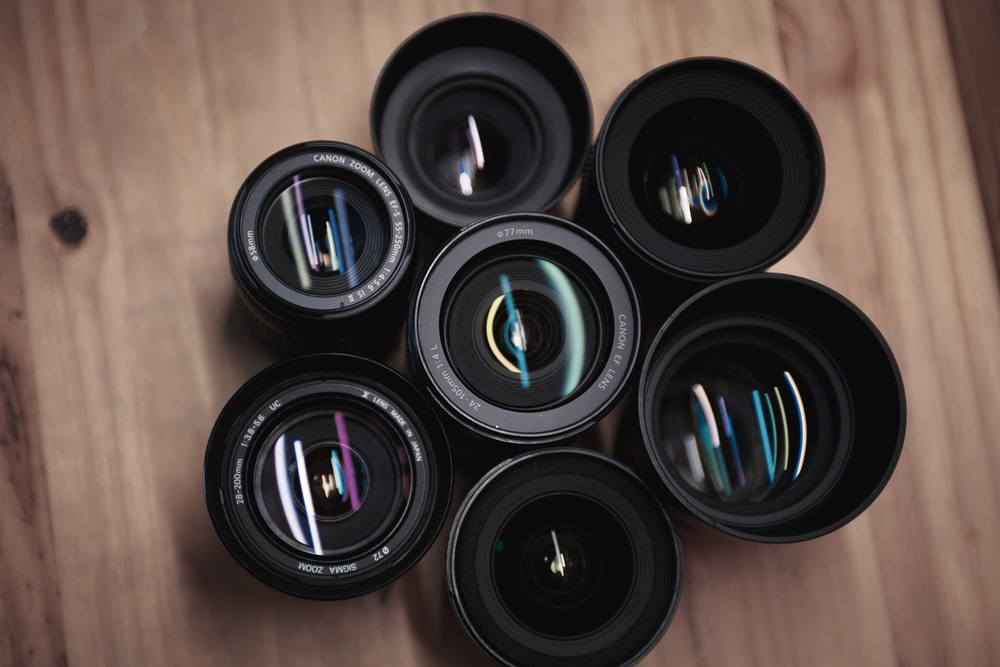 seven black camera zoom lenses on table