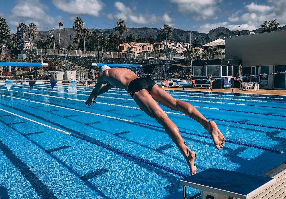 man diving in pool during daytime