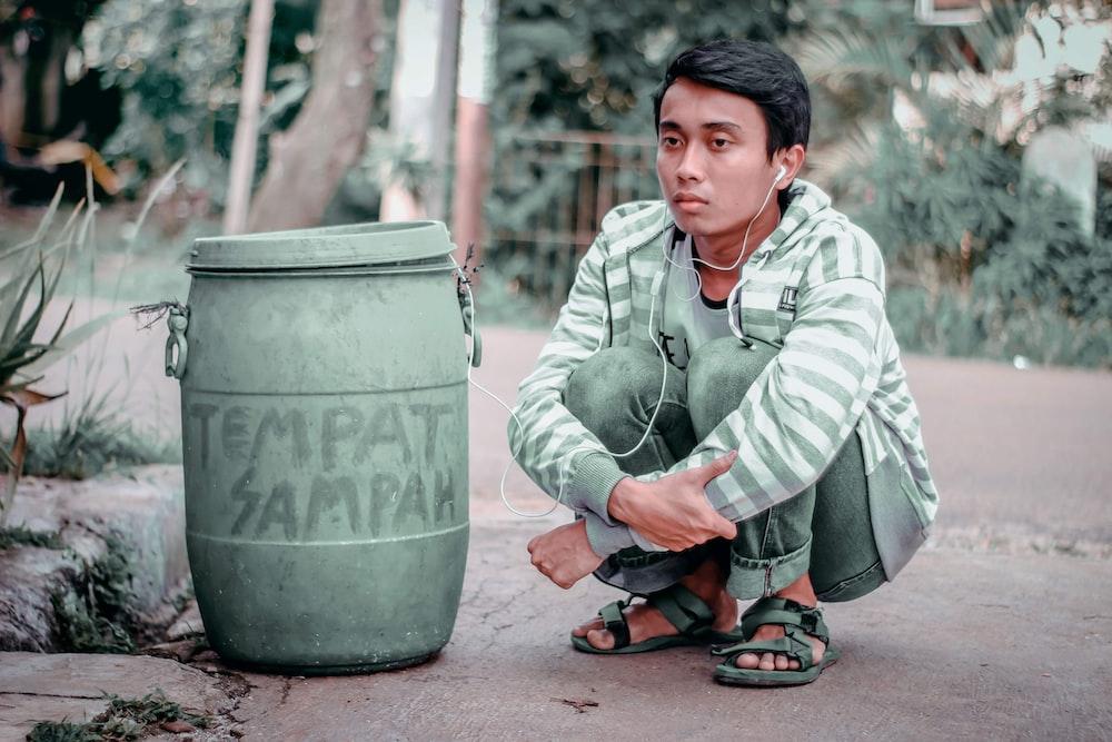 man sitting beside trash bin during daytime