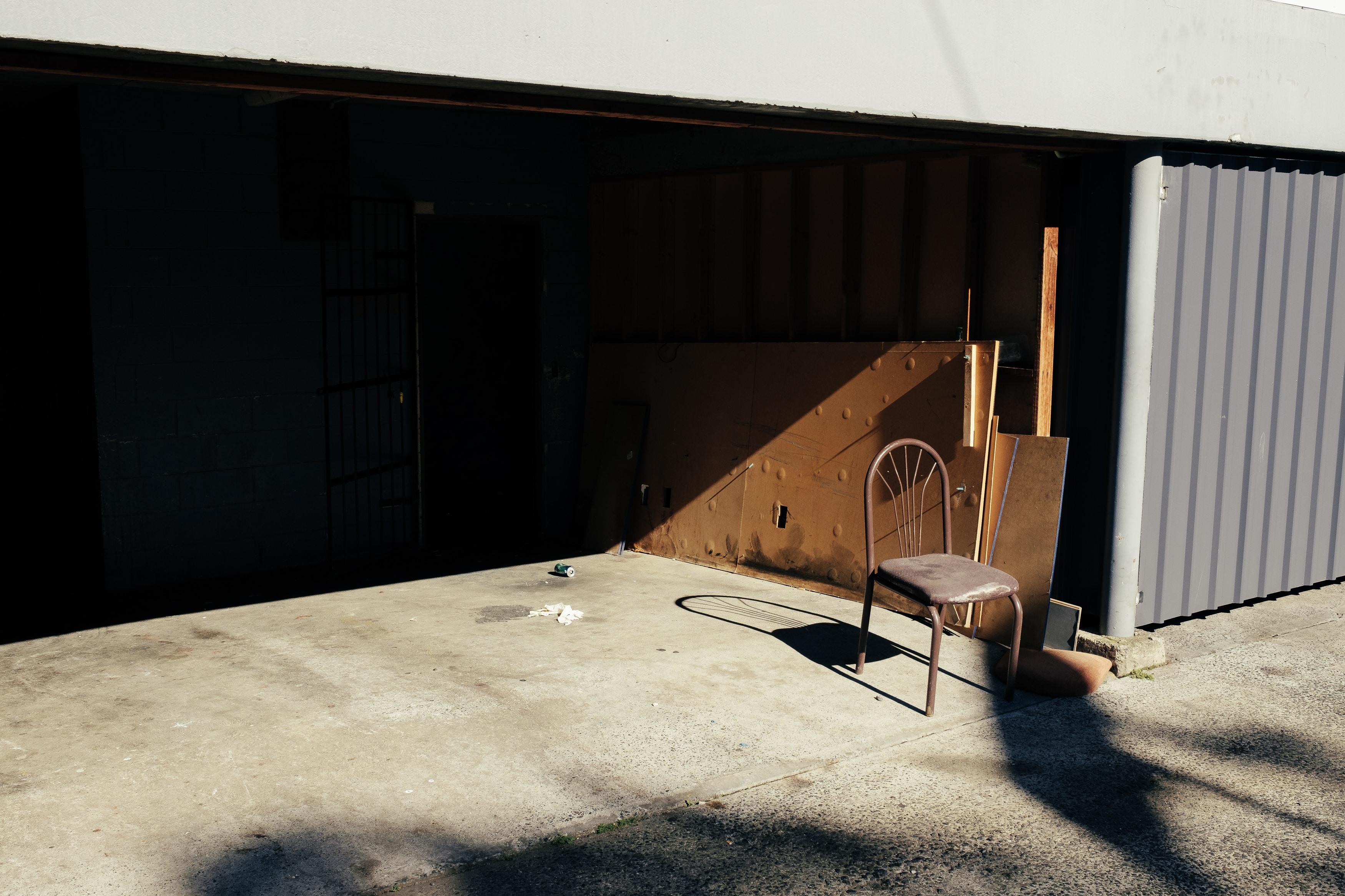brown metal armless chair on garage
