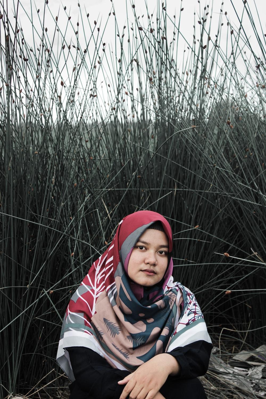 woman sitting beside green grass