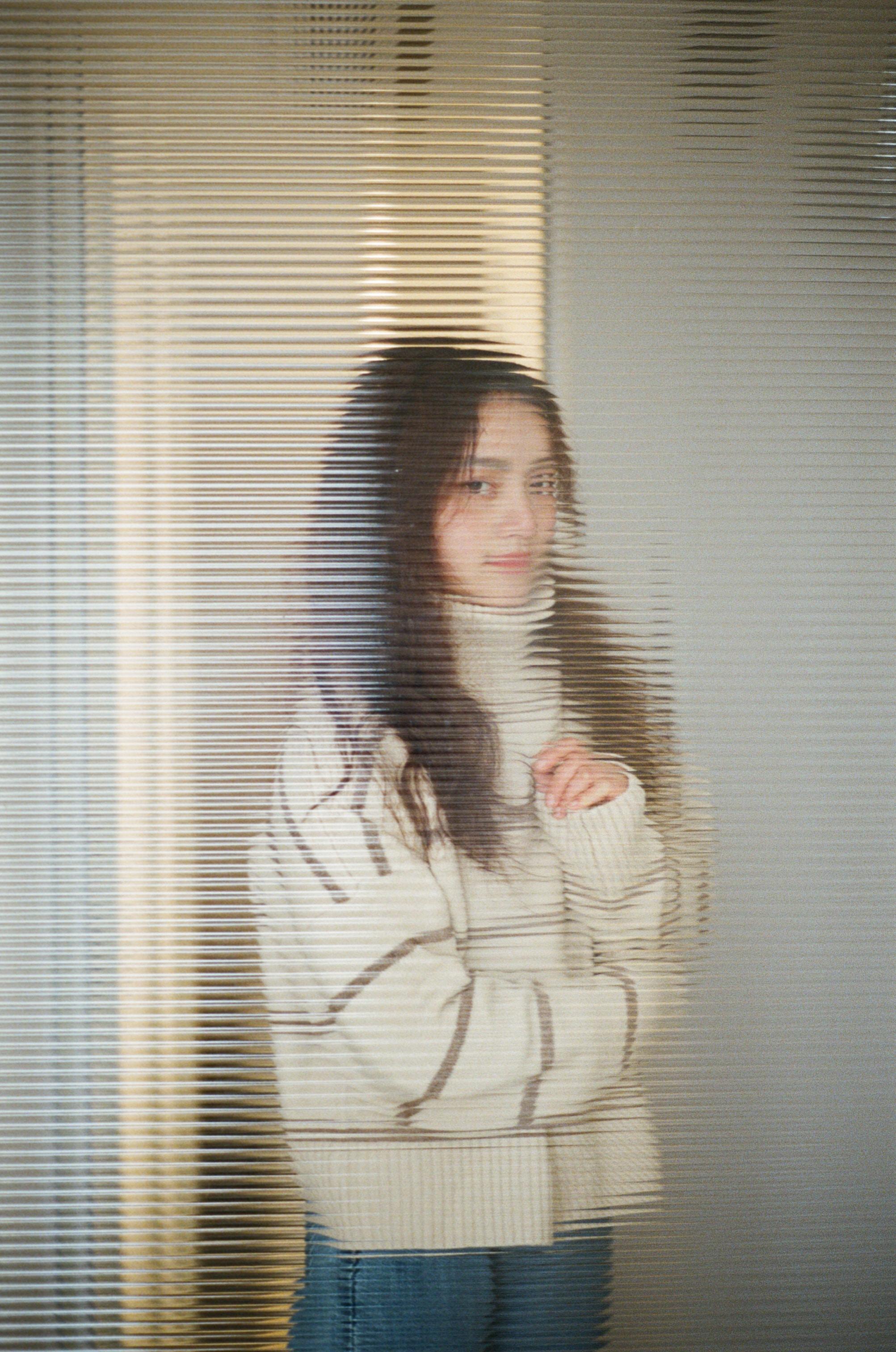 woman standing beside gray wall