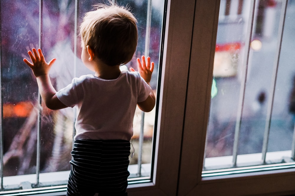 toddler leaning on glass door