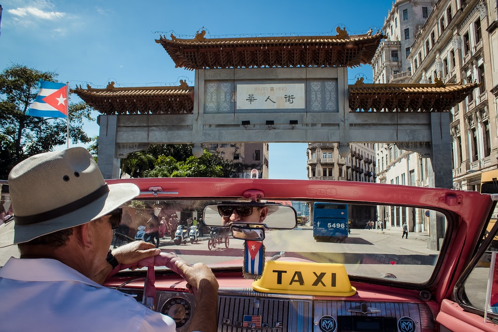man driving red Taxi during daytime
