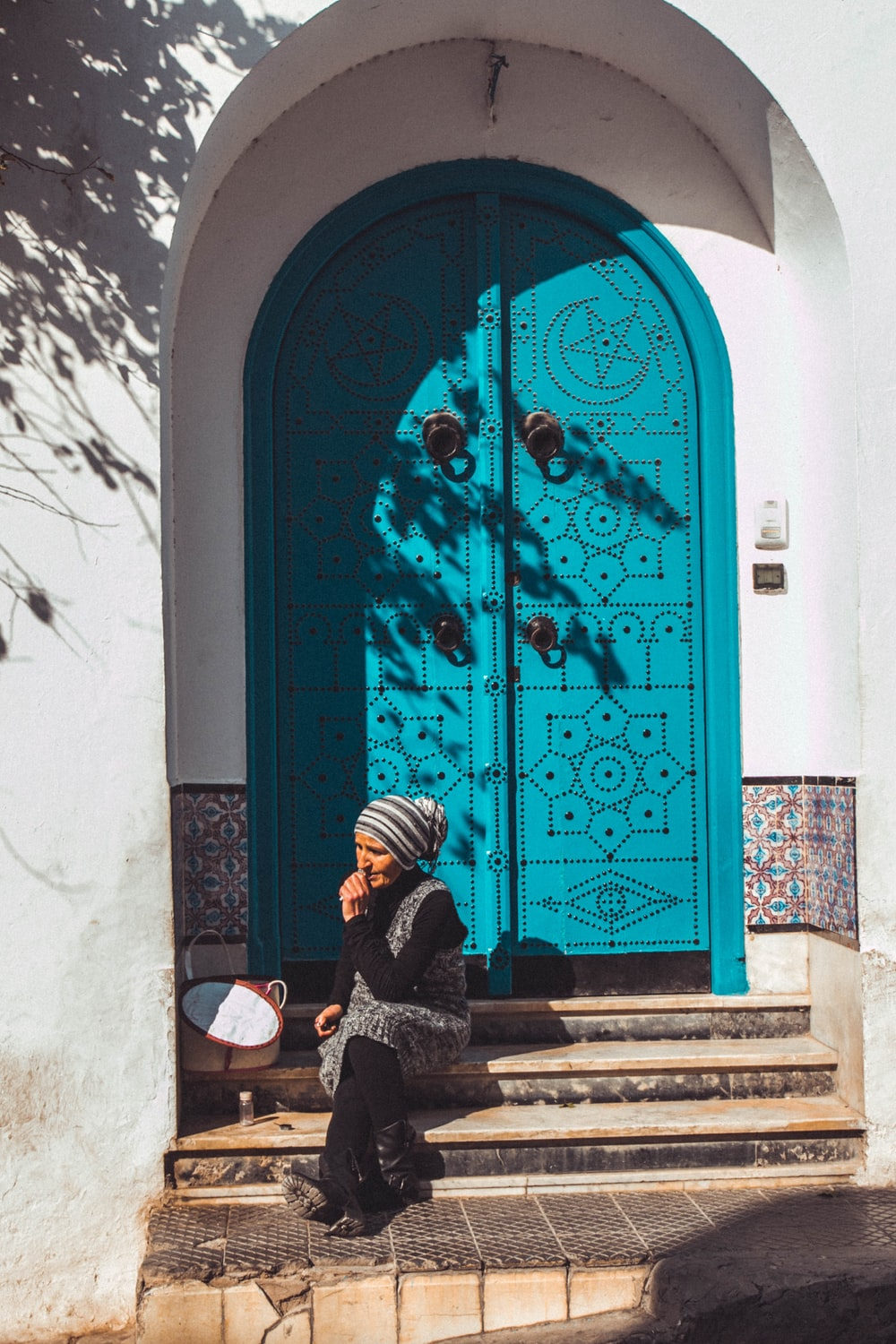 woman sitting beside blue wooden door
