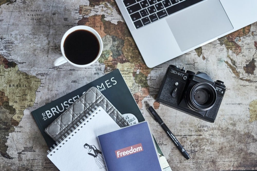 black camera beside laptop and mug