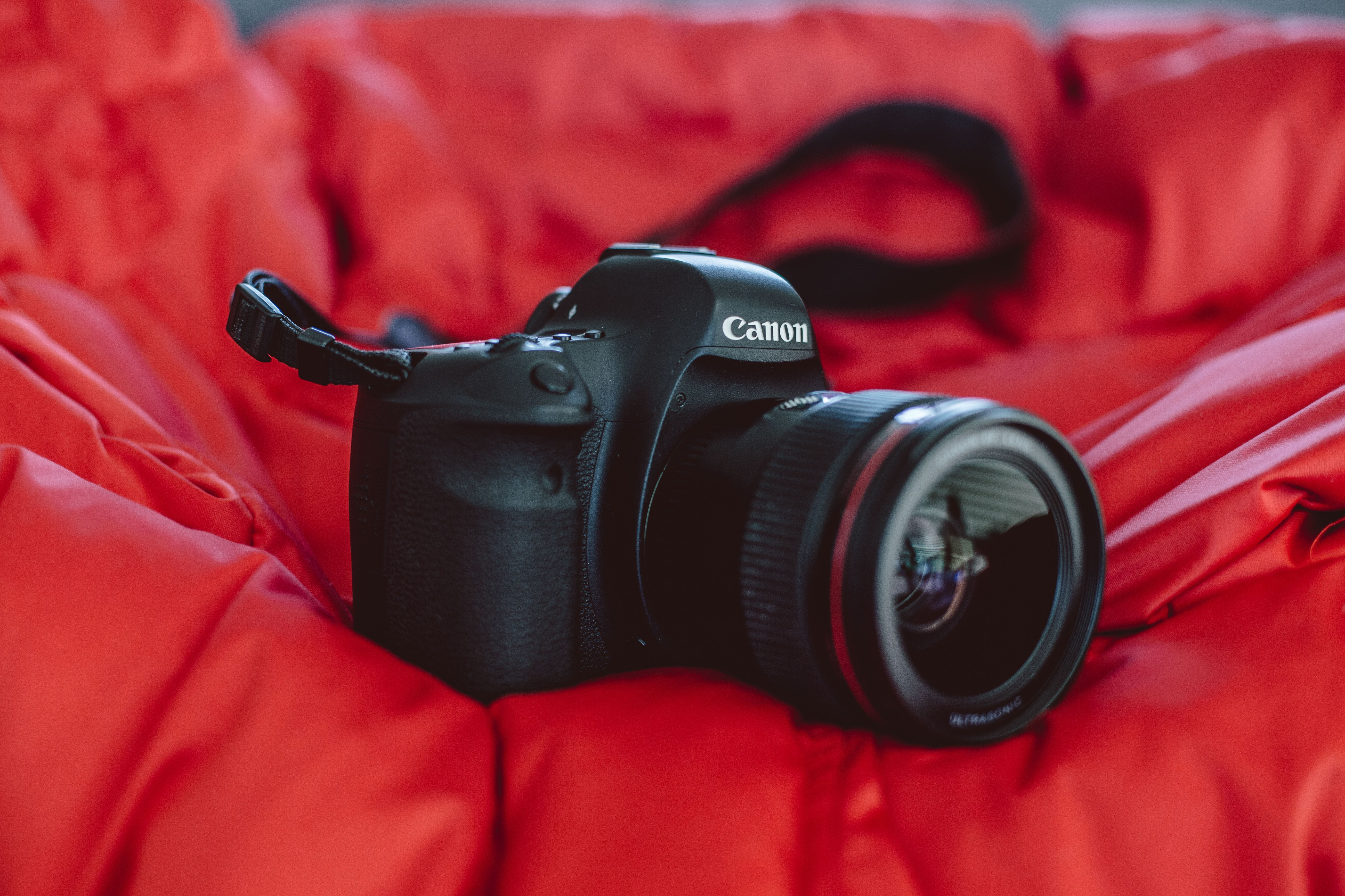 selective focus photography of black Canon DSLR camera on red textile