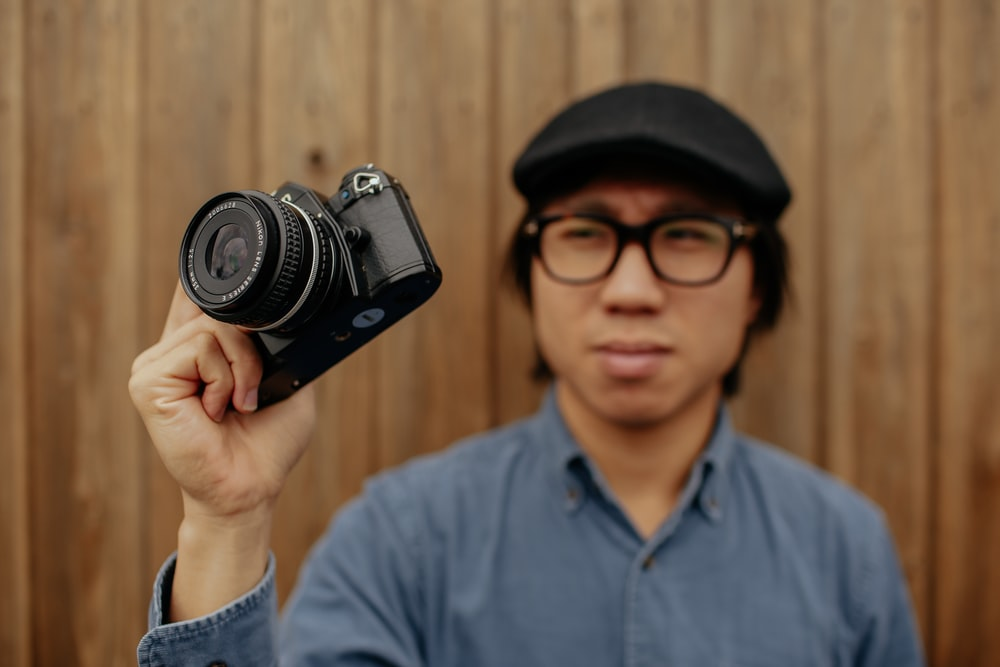 man standing while holding black camera
