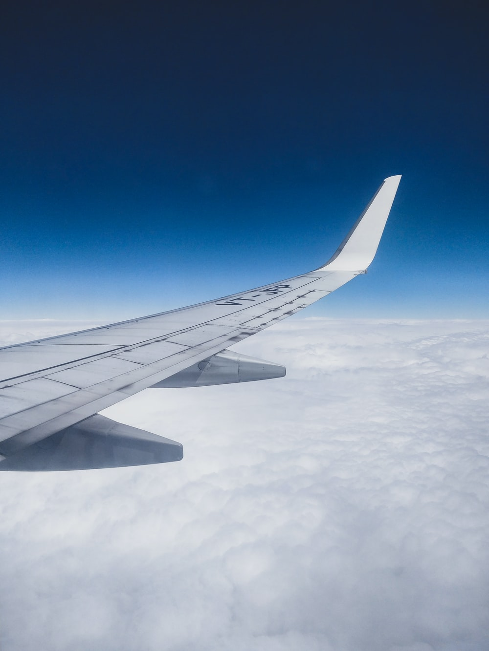 close-up photography of white plane wing on sky