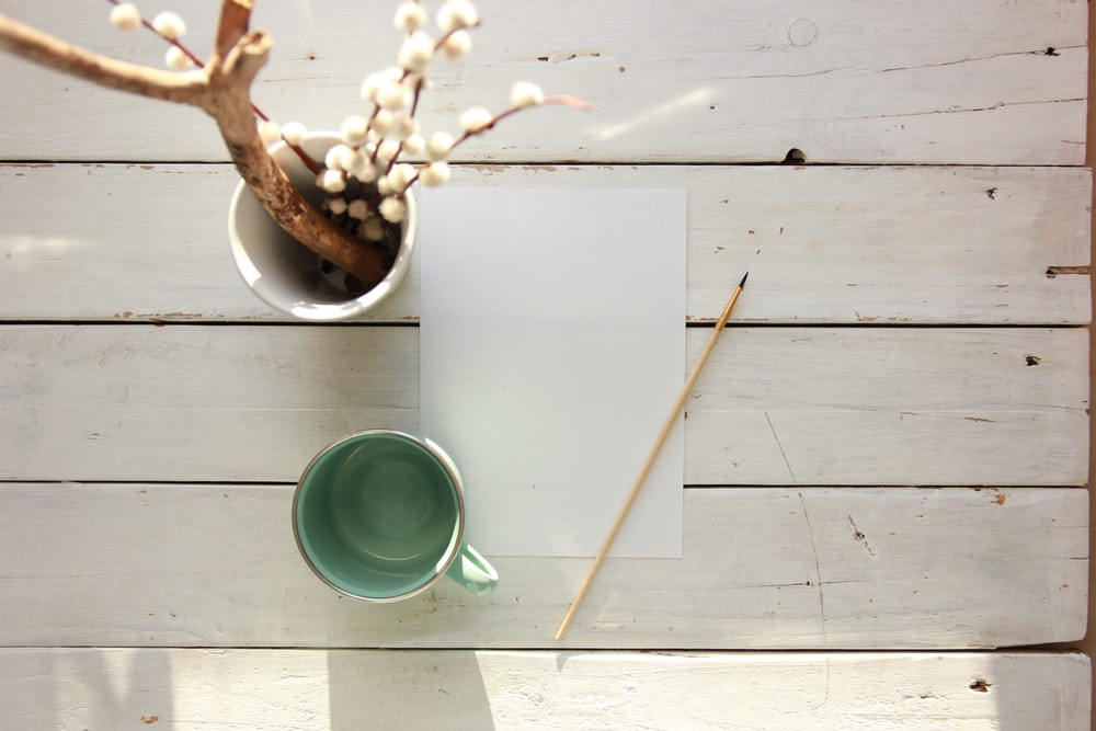 green ceramic cup on white paper