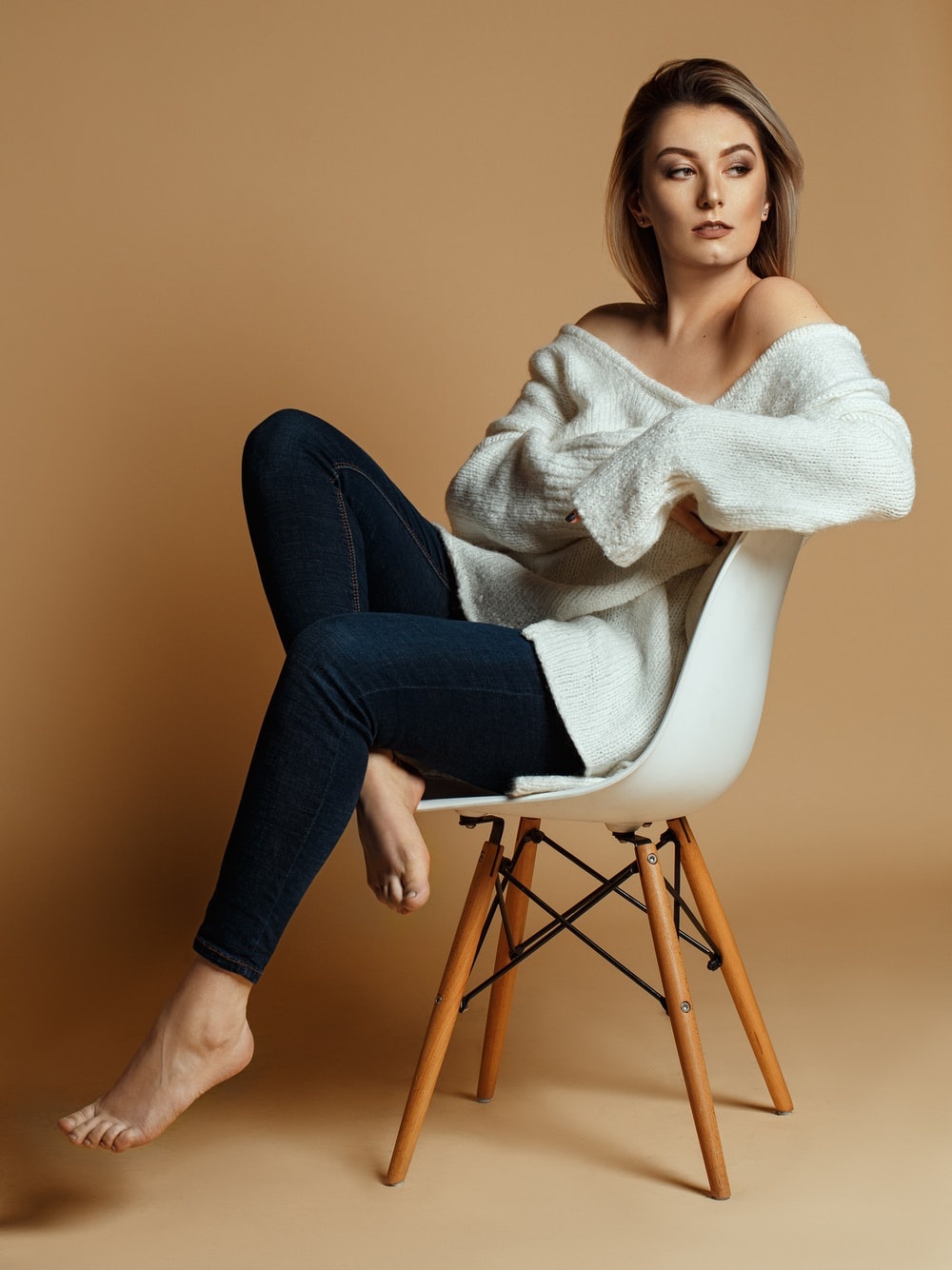 woman sitting on brown and white wooden chair