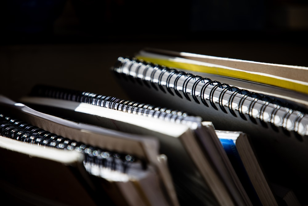 selective focus photography of spiral notebooks