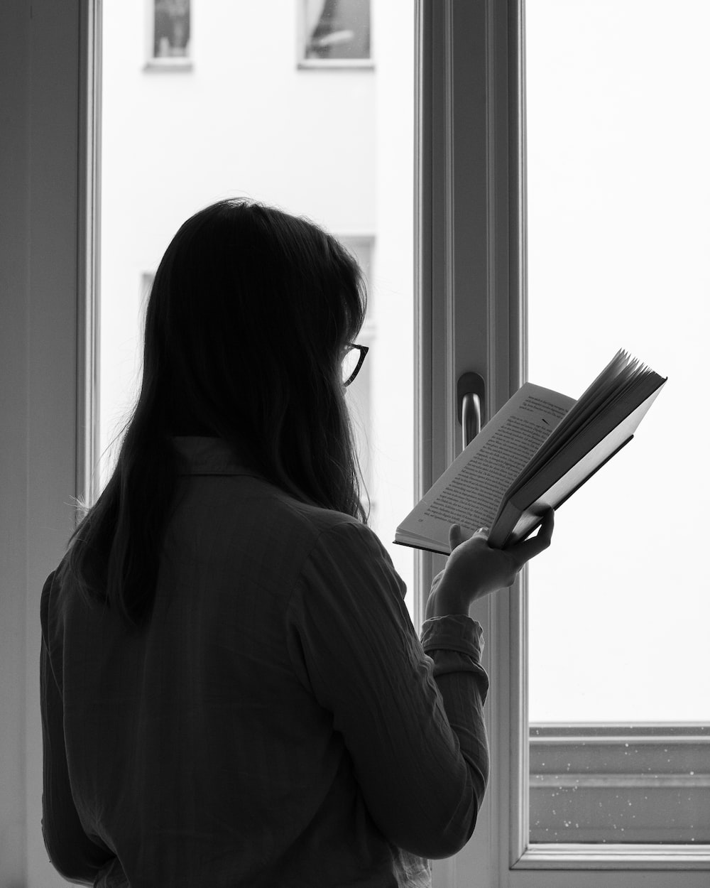 grayscale photo of woman holding book beside window
