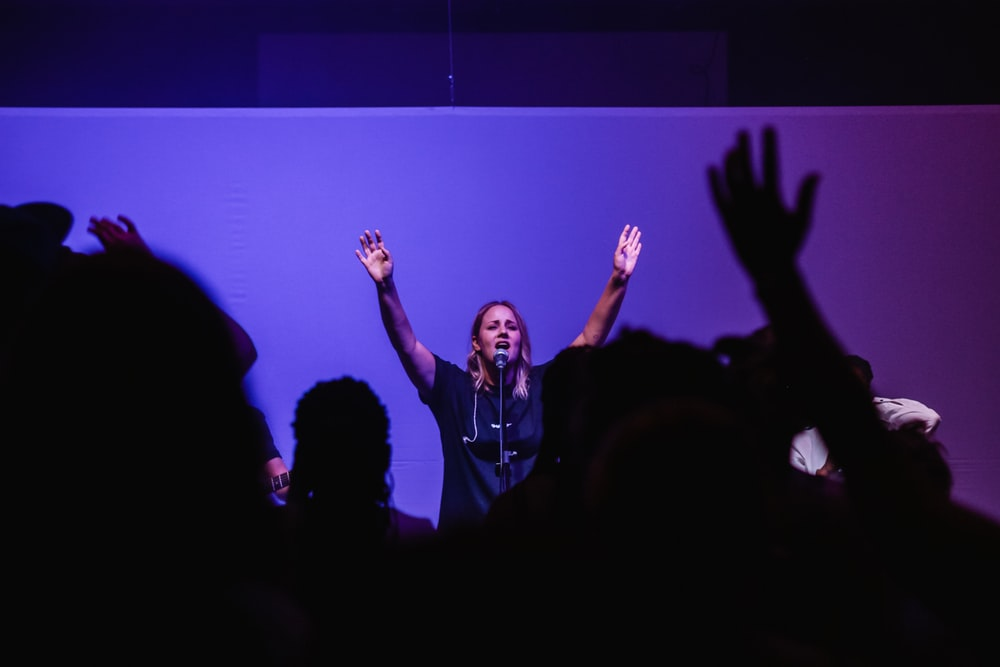 woman raising both hands in front of people