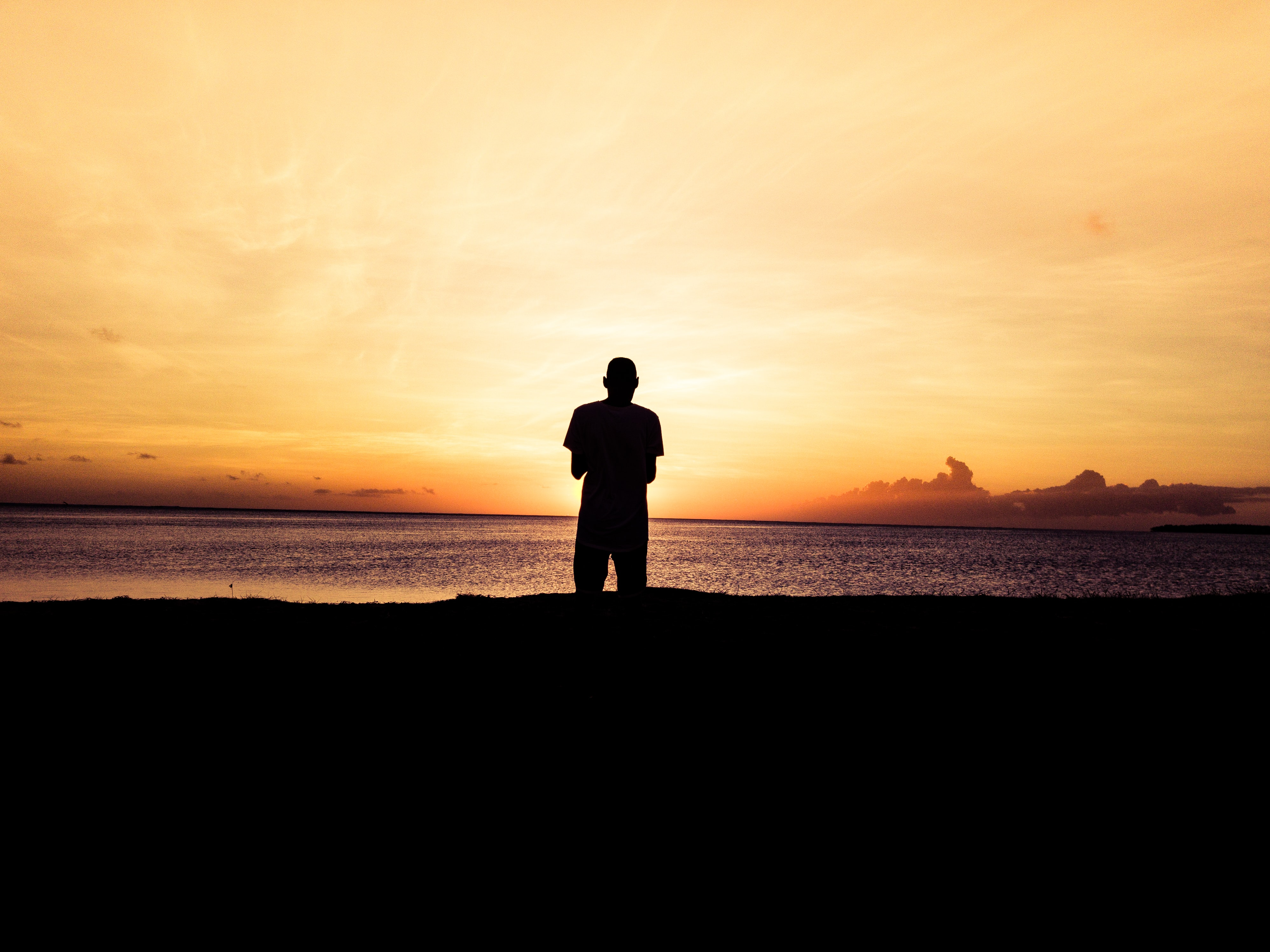 silhouette photo of person standing in front of body of water during sunset