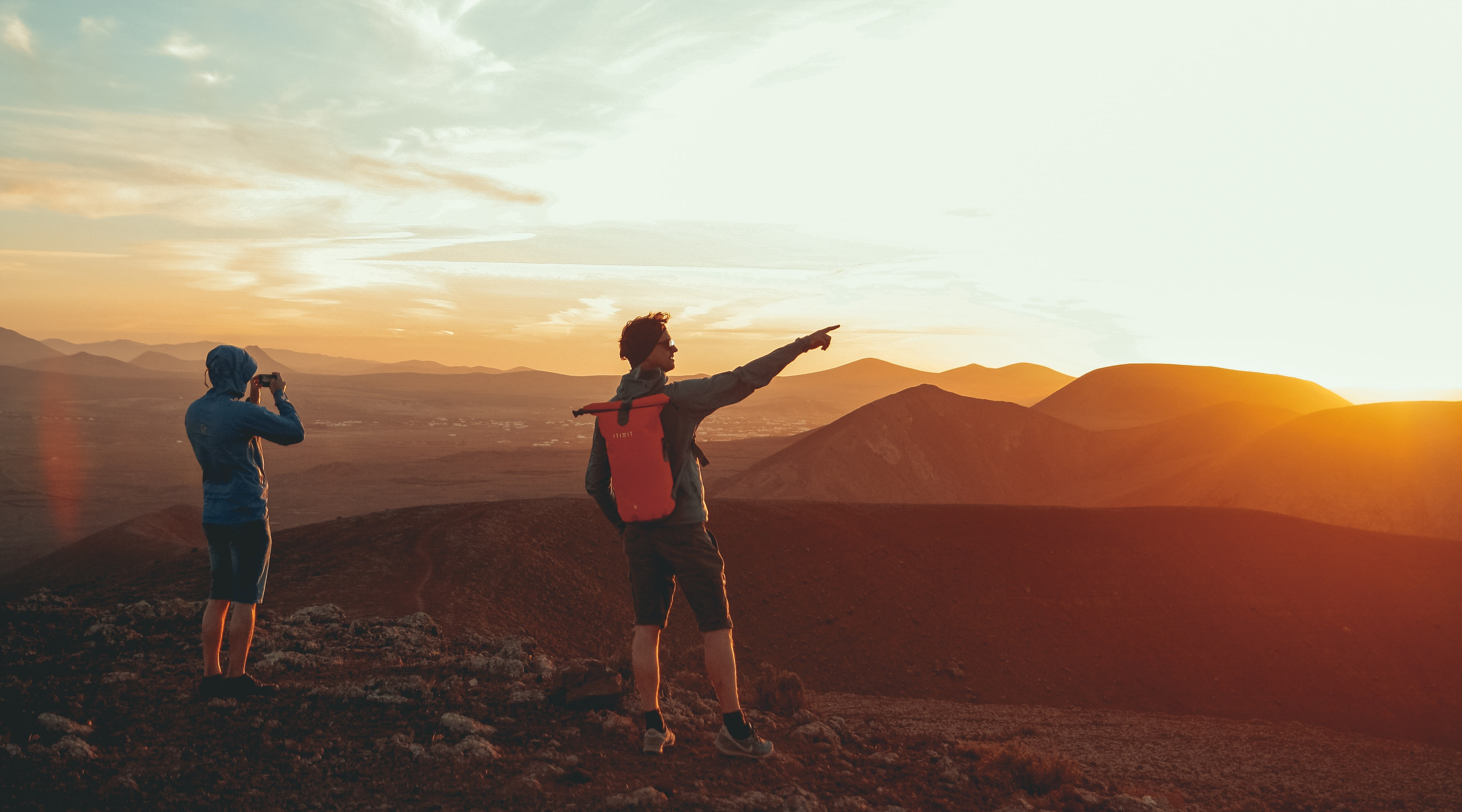 two person standing on mountain during sunset