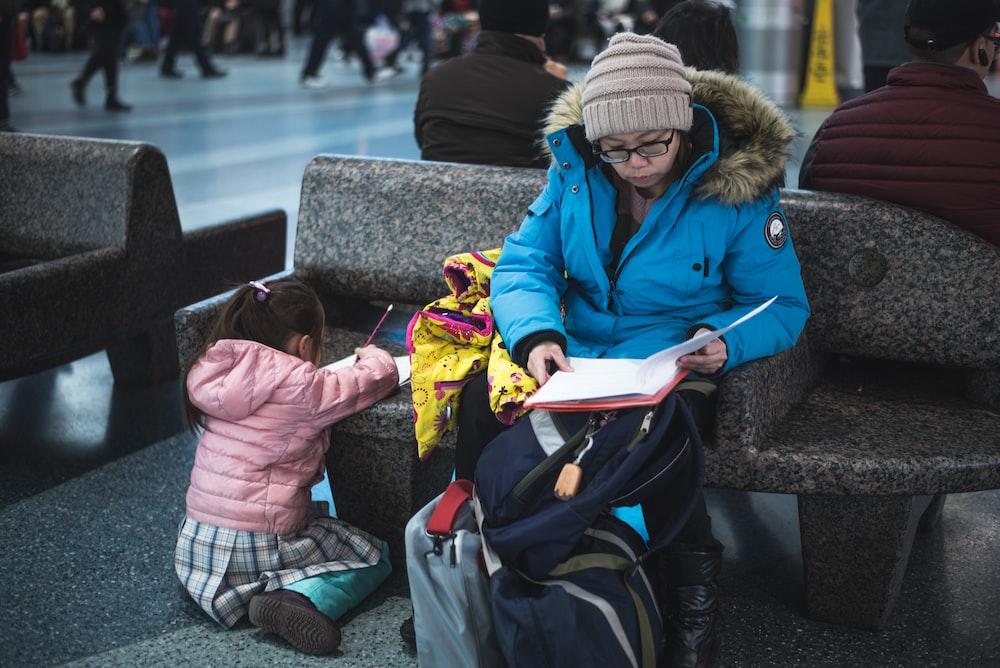 woman sitting beside girl writing on bench