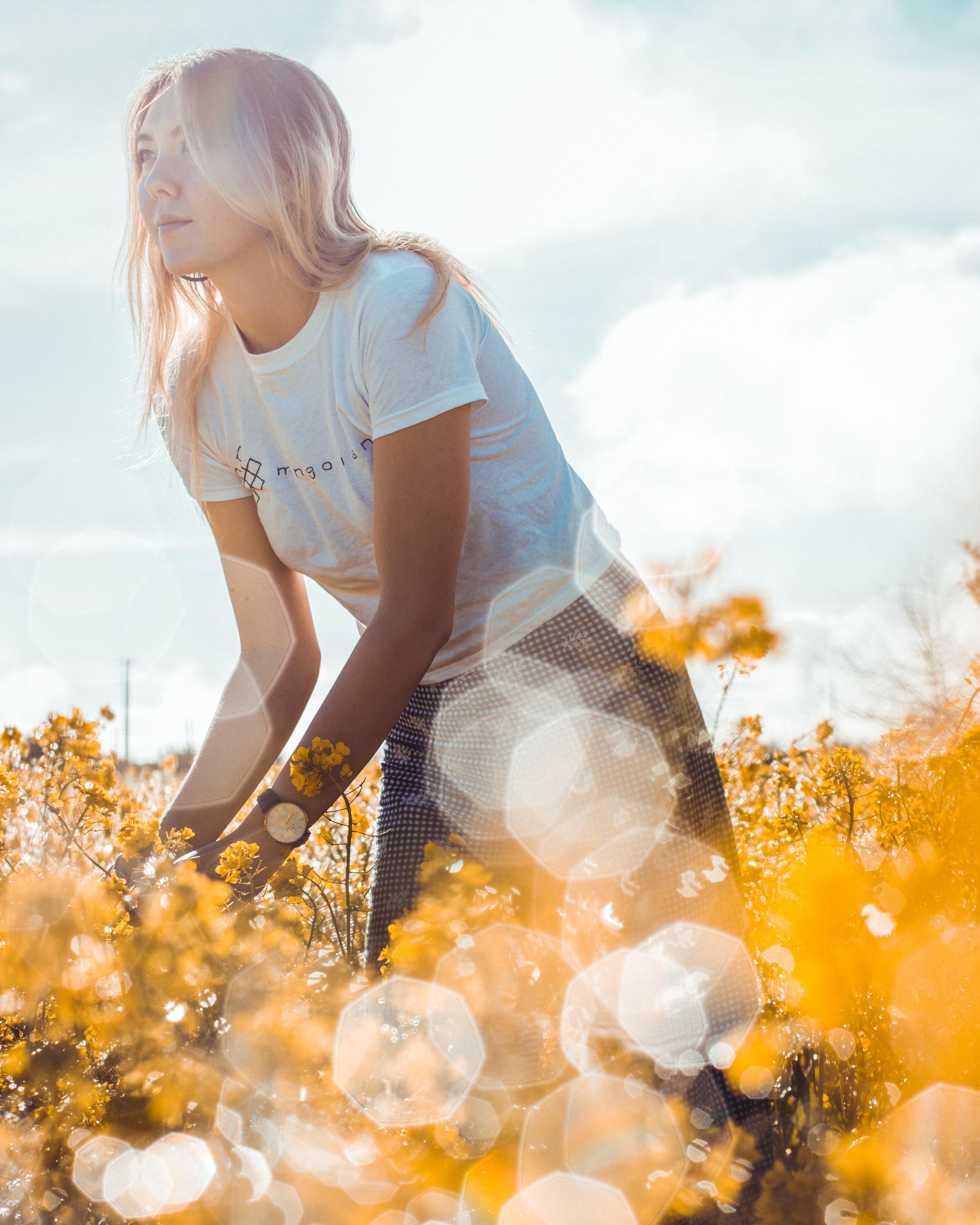 woman standing on yellow flower field