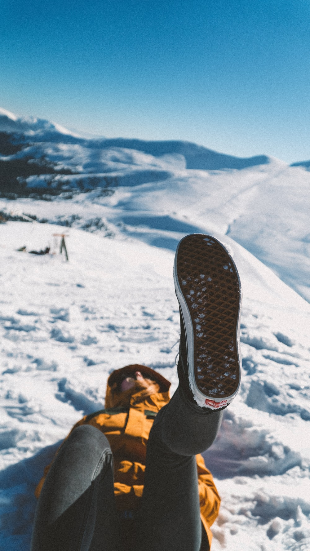 person lying on snow during day