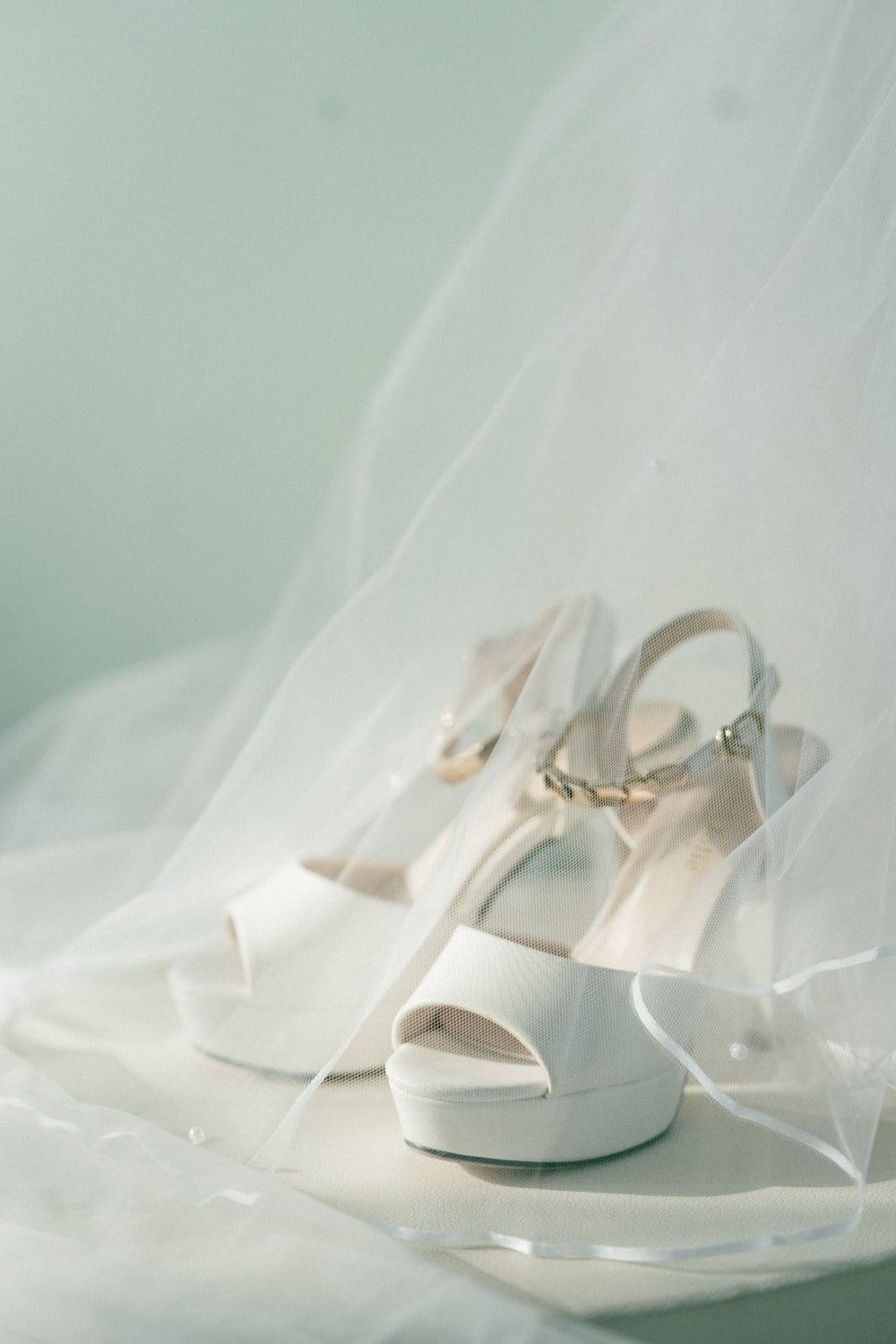 white open-toe sling-back high-heeled sandals covered with white veil