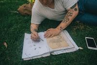man wearing grey shirt lying on grass drawing