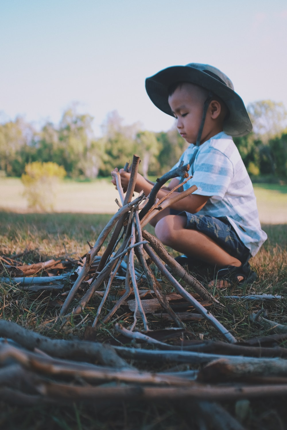boy squat sitting beside wooden sticks formed to a pyramid during day