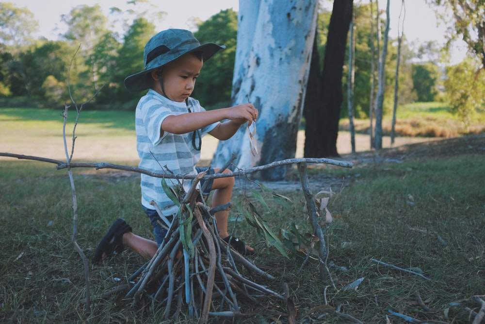 boy wearing gray hat, white-and-gray striped crew-neck t-shirt and gray shorts kneeling on ground playing twigs during daytime