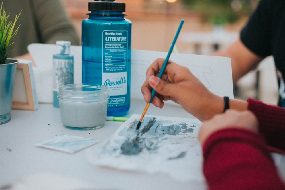 person holding blue paint brush painting on paper on table