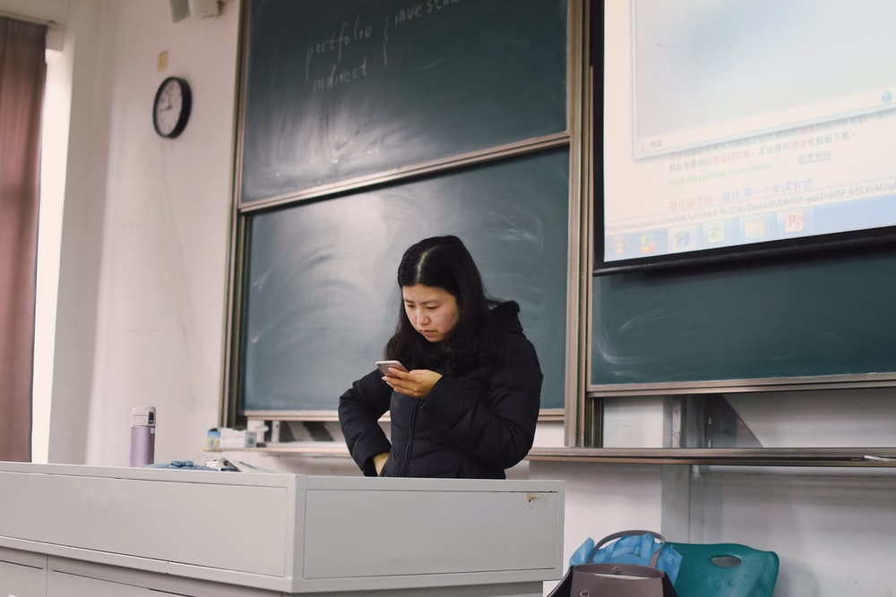 woman wearing black hoodie using smartphone near chalk board