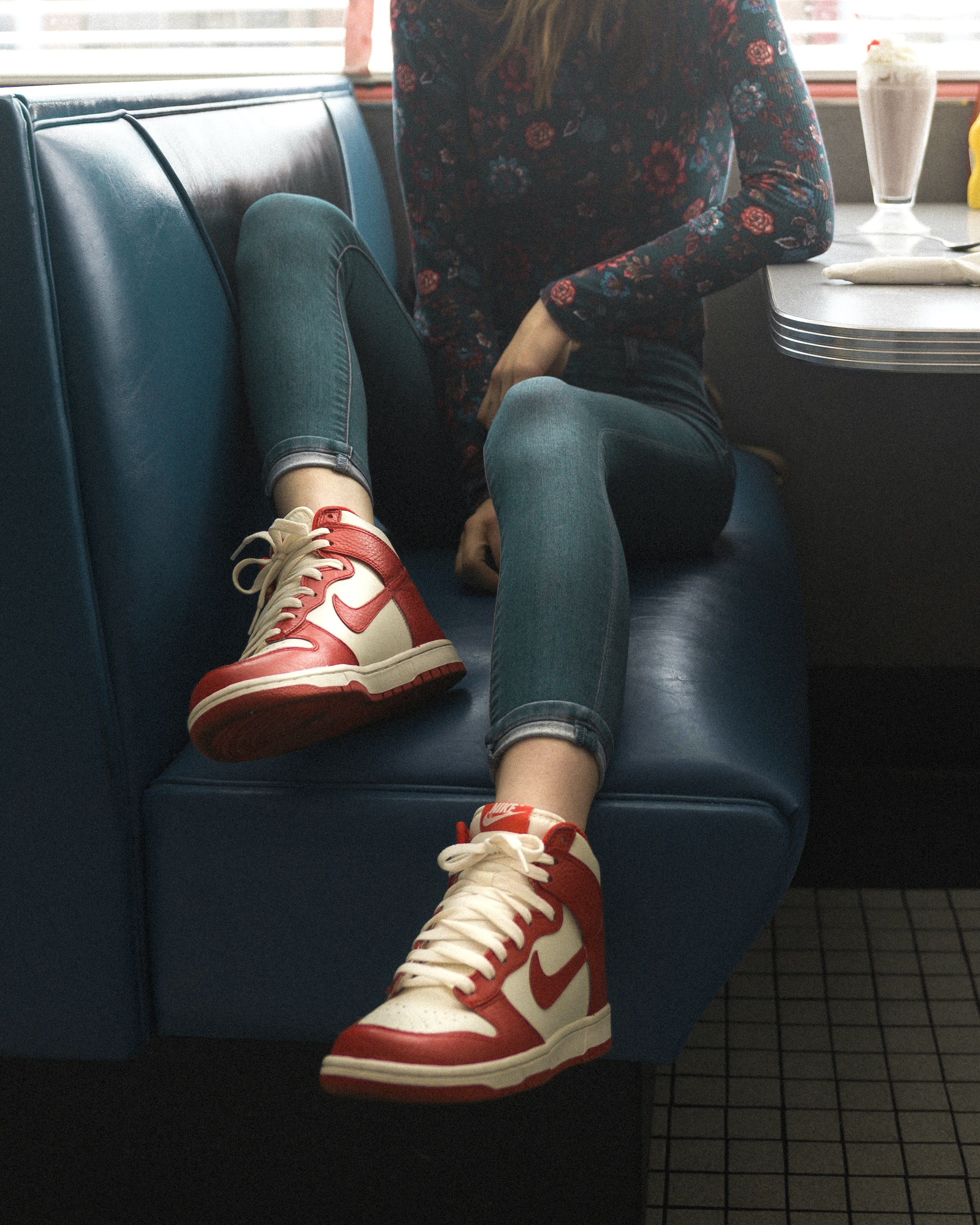 woman wearing red-and-white Nike mid-top sneakers while sitting on seat
