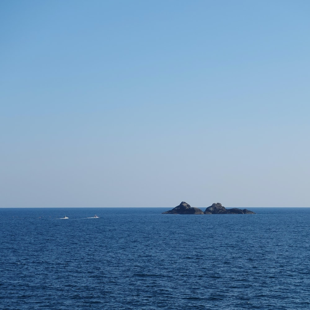 two boats on water near islet during daytime