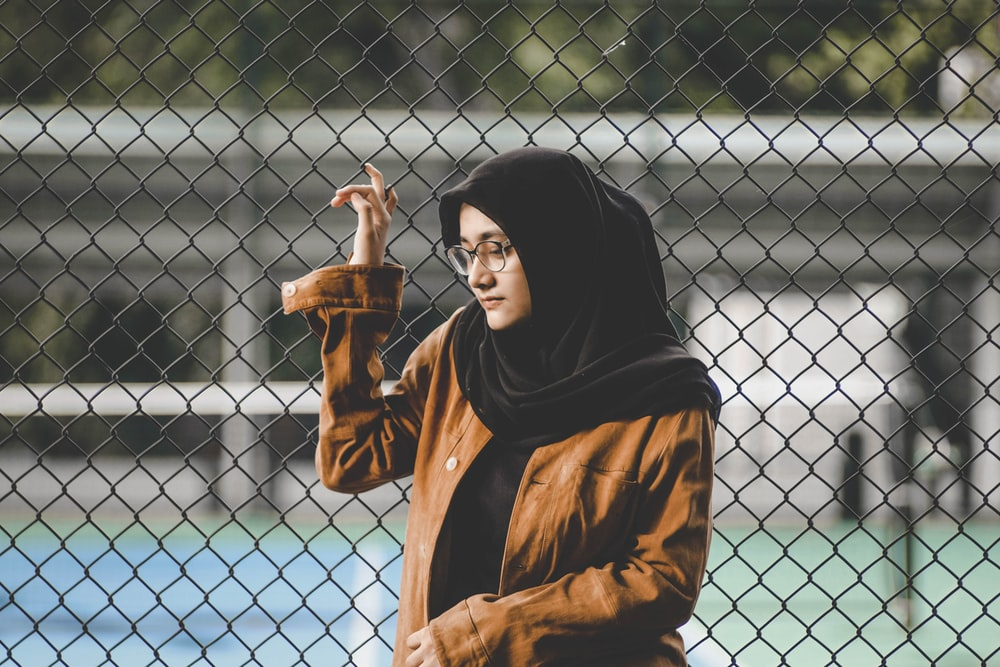 selective focus photography of woman wearing black hijab scarf and brown coat leaning on metal chain-link fence during daytime