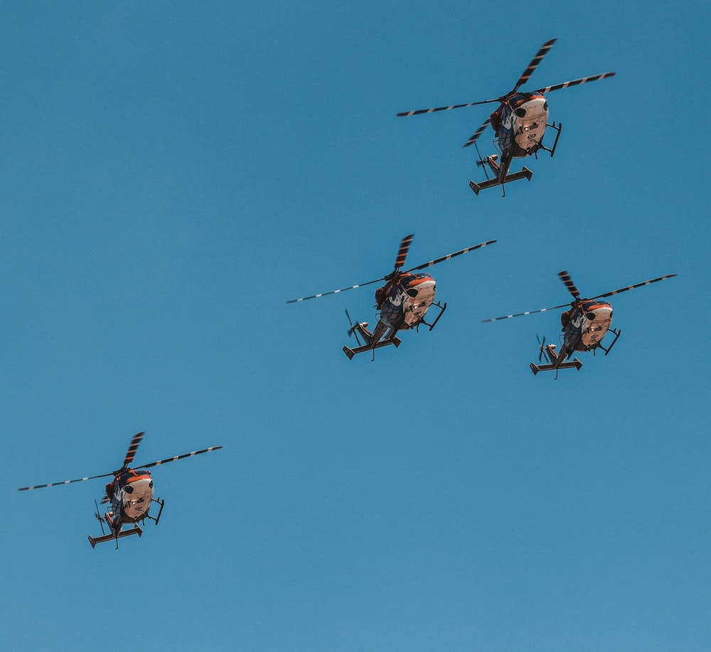 four helicopters flying
