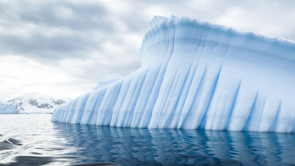 iceberg near mountain during day