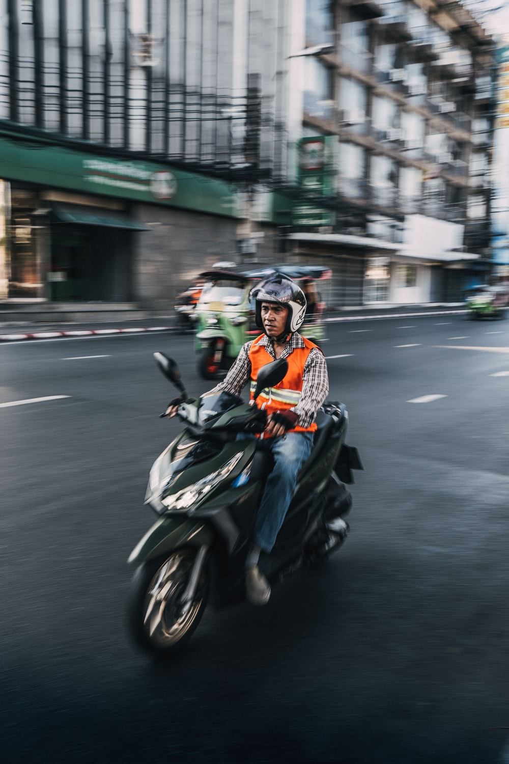 man driving scooter motorcycle during daytime