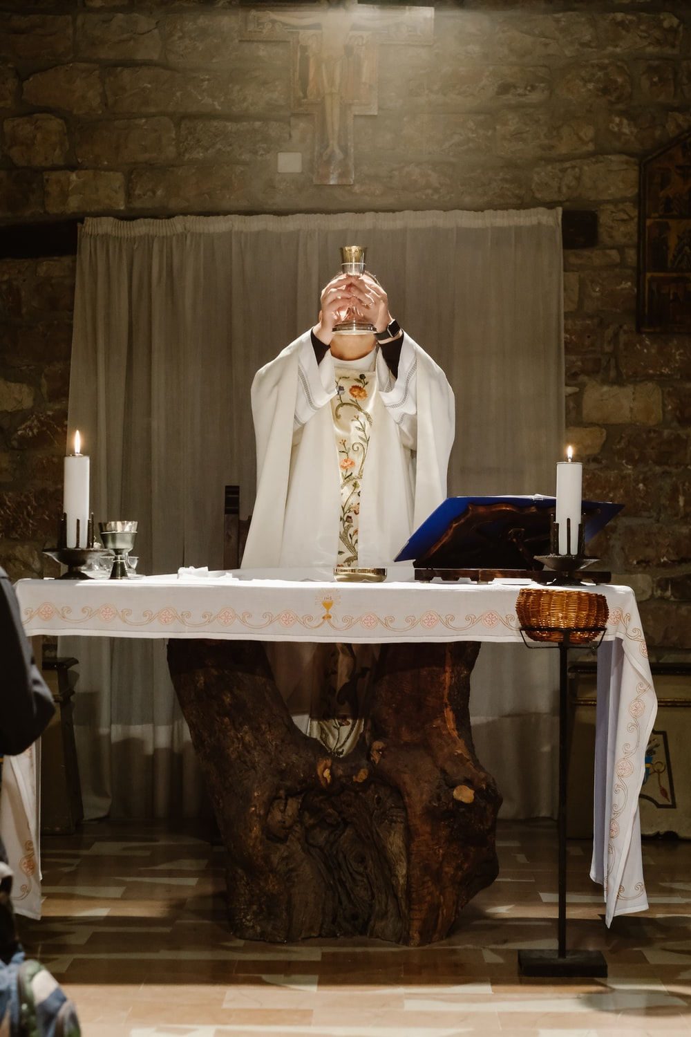 priest lifting goblet while standing beside table