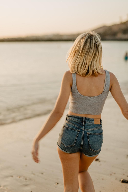 woman wearing gray tank top and blue denim short shorts walking on shore during daytime