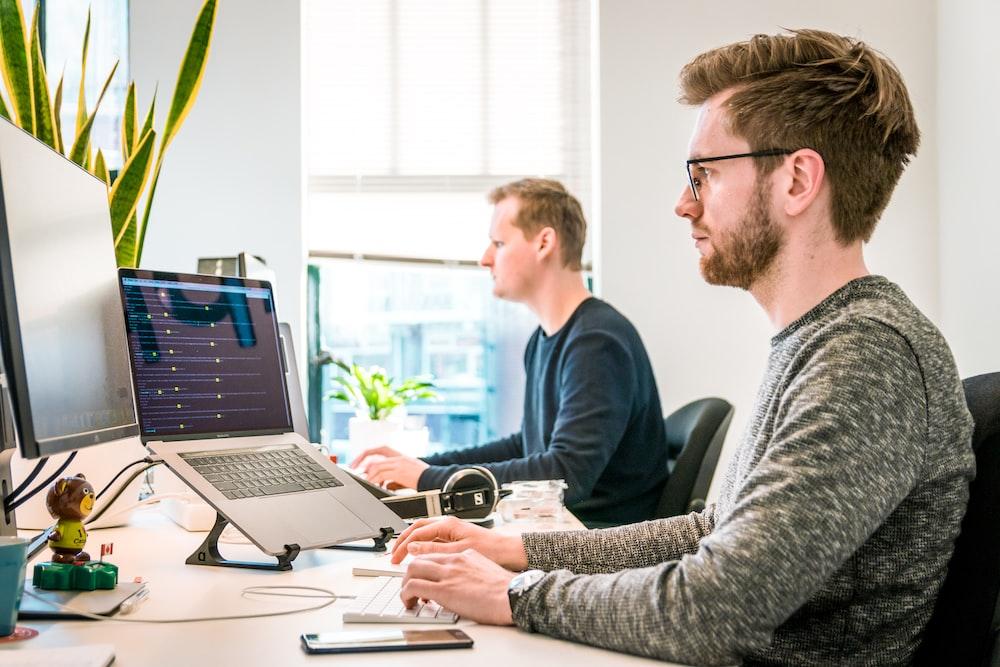 man sitting on chair wearing gray crew-neck long-sleeved shirt using Apple Magic Keyboard