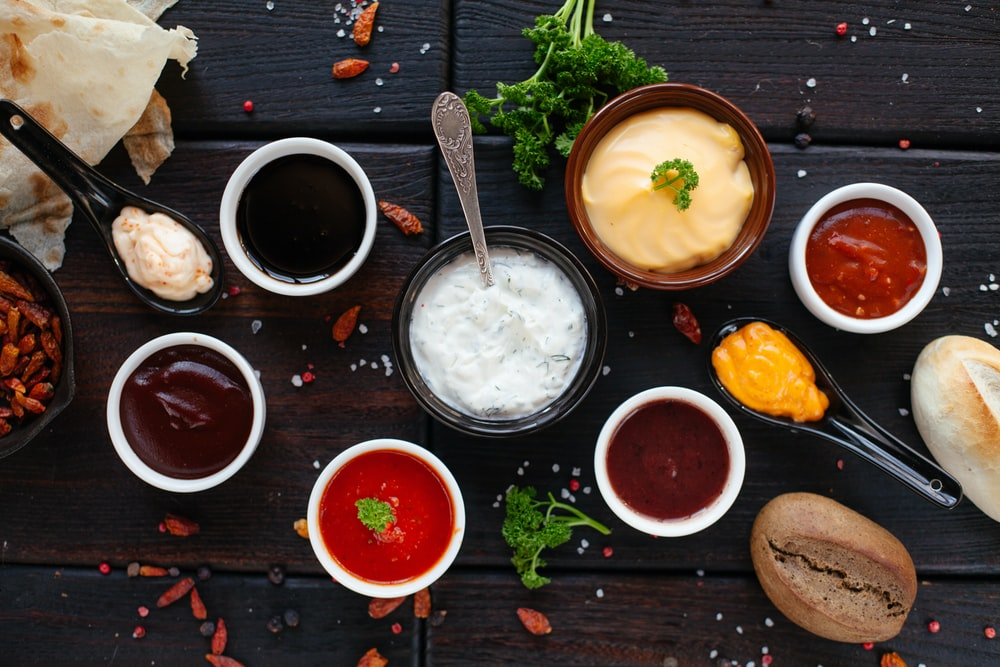 assorted spices on bowls on black wooden surface