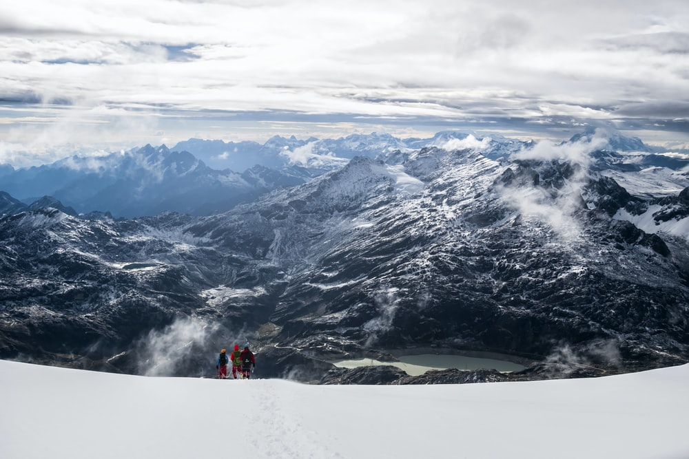 aerial photography of three people on top of snow-covered mountain during daytime