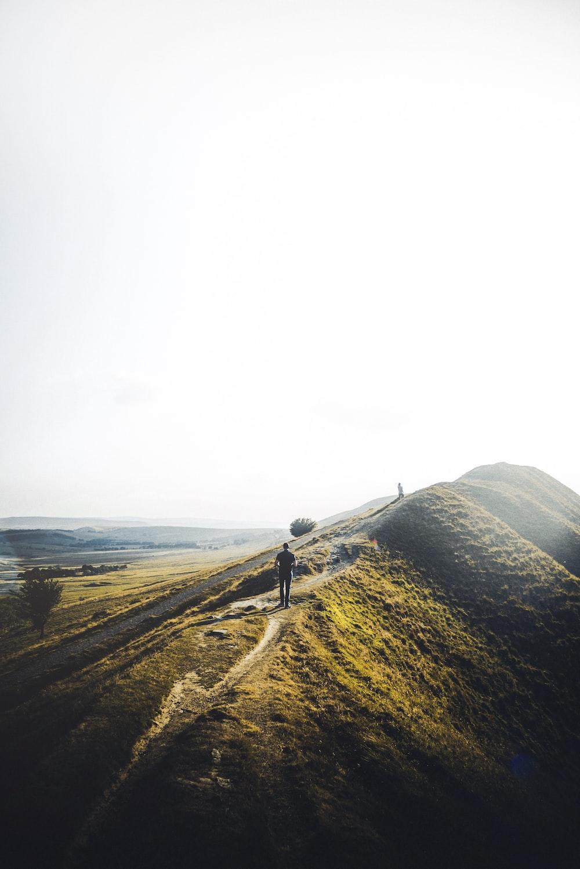 man walking on green mountain