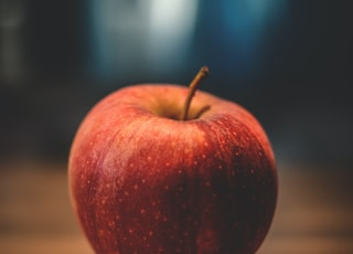 red apple on brown surface