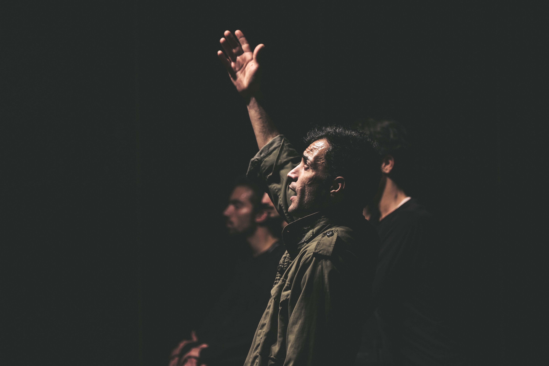 man raising a right hand beside men