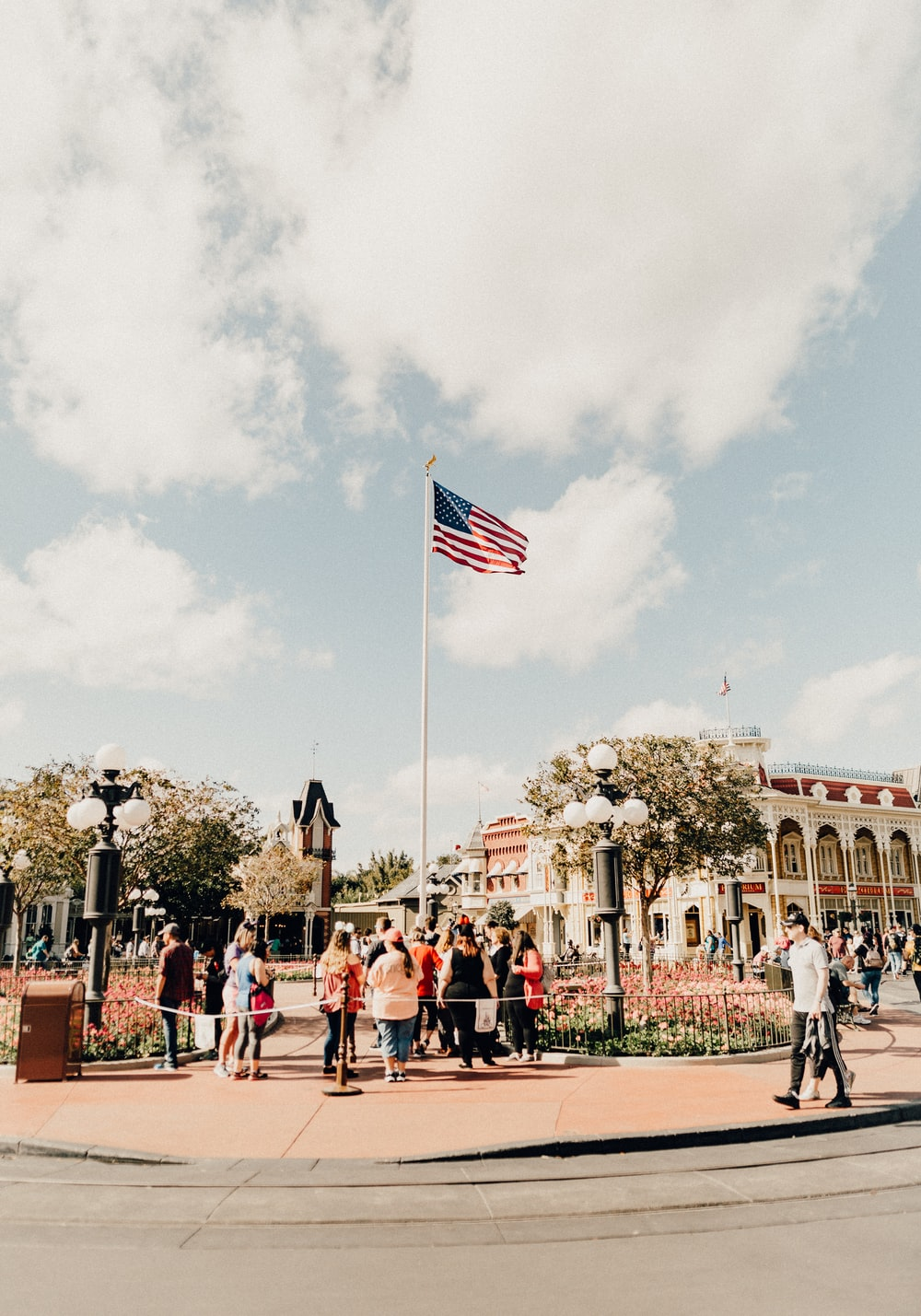 people standing and woman walking and standing by pole with USA flag