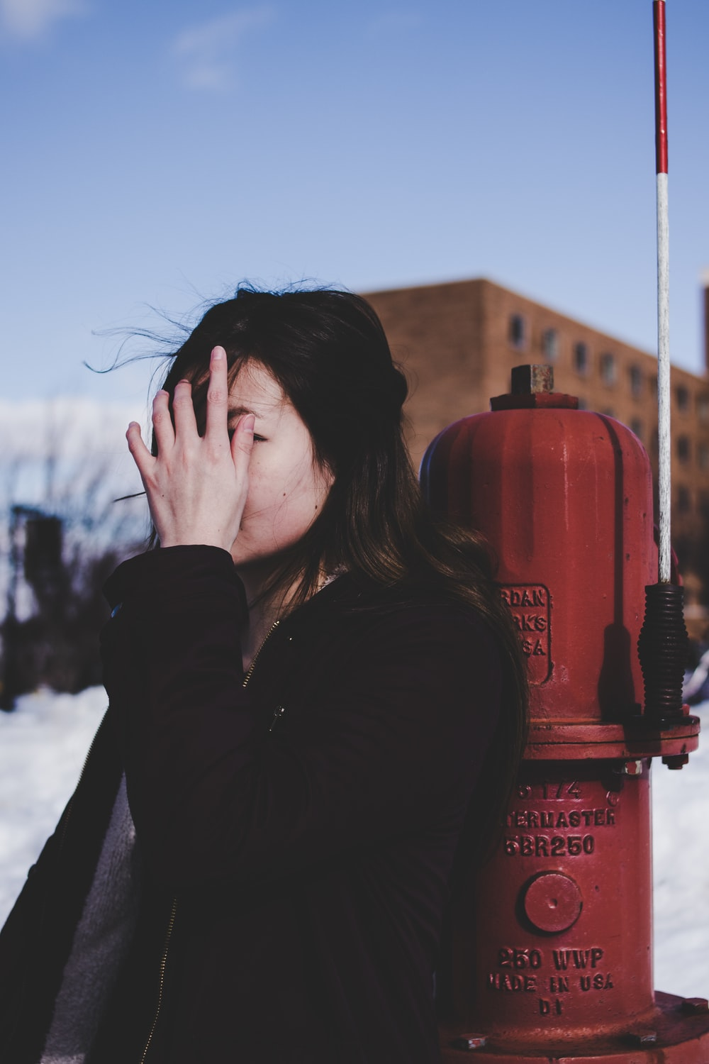 woman leaning beside red fire hydrant