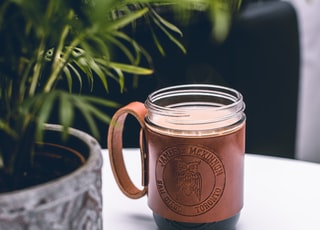brown and clear glass mug on white surface