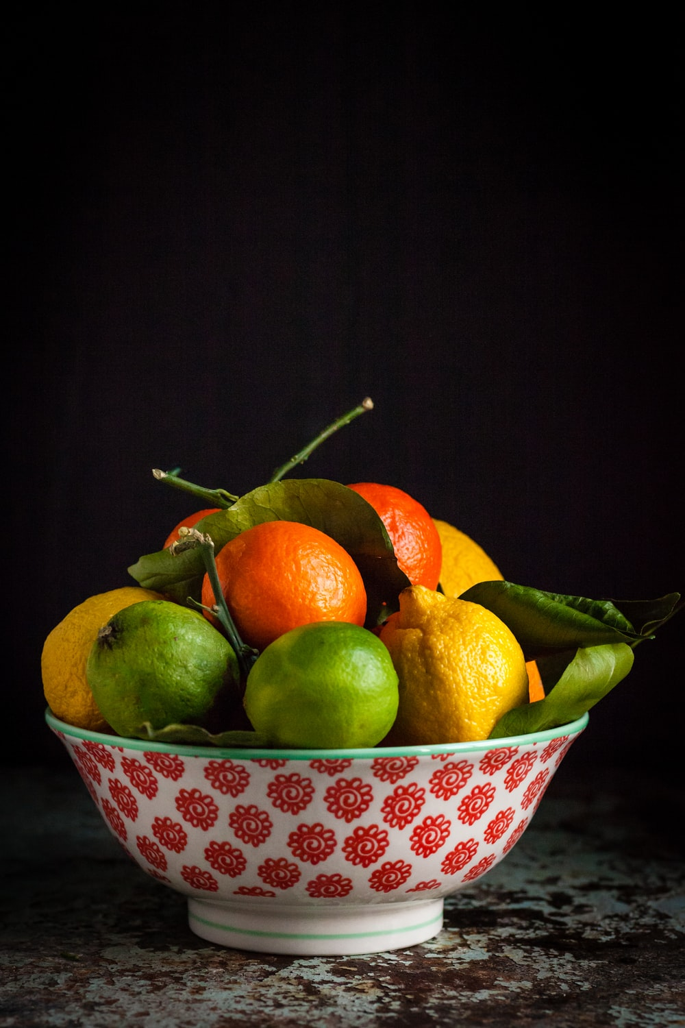orange and green fruits on bowl