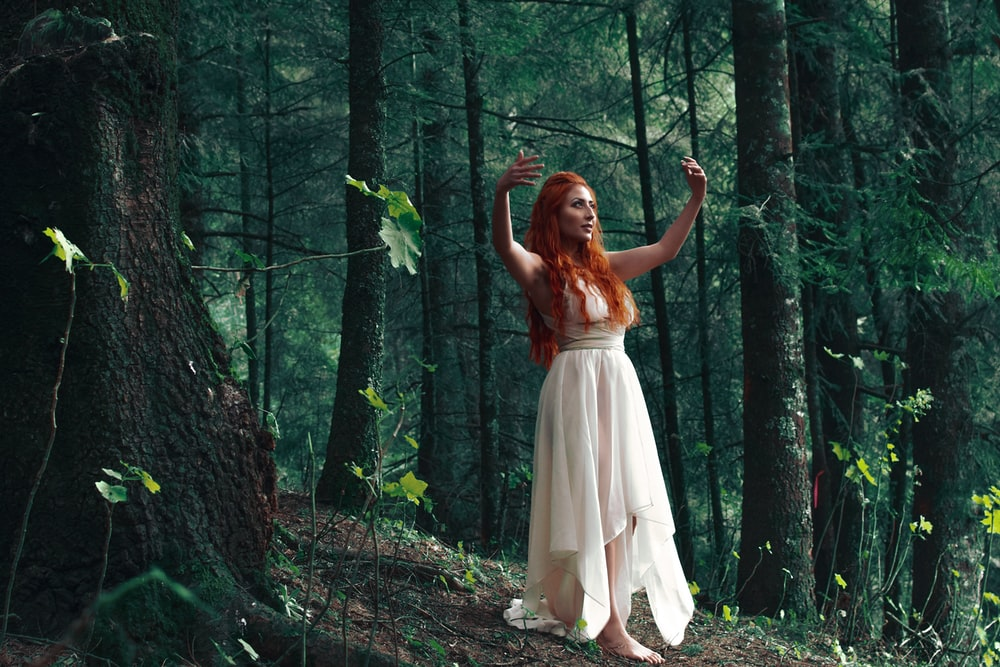 woman wearing white high-low dress in middle of woods during daytime