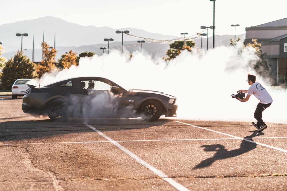 person riding on gray coupe doing drifting